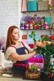 La ragazza che lavora in un negozio di fiore, donna del fiorista fa un mazzo Immagine Stock Libera da Diritti