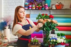 La ragazza che lavora in un negozio di fiore, donna del fiorista fa un mazzo Fotografie Stock