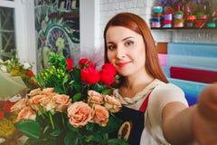 La ragazza che lavora in un negozio di fiore, Floristry fa la foto del selfie con un mazzo dei fiori Fotografia Stock Libera da Diritti