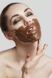 La ragazza che lecca il cioccolato spalmato Fotografie Stock