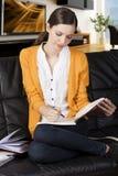 La ragazza che legge un libro con il axpression assorbente Immagini Stock
