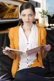 La ragazza che legge un libro, osserva dentro all'obiettivo Immagini Stock