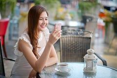 La ragazza che manda un sms sullo Smart Phone in un terrazzo del ristorante con Fotografia Stock Libera da Diritti