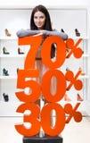 La ragazza che mostra la percentuale delle vendite sul livello ha tallonato le scarpe Fotografie Stock