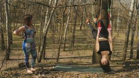 La ragazza che pratica il aerogravity si esercita all'aperto con l'istruttore archivi video