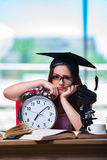 La ragazza che prepara per gli esami con il grande orologio Immagine Stock