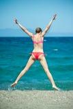 La ragazza che salta alla spiaggia Fotografia Stock