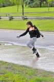 La ragazza che salta attraverso l'inondazione sulla strada Immagine Stock