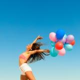 La ragazza che salta con i palloni variopinti sul fondo del cielo Fotografia Stock