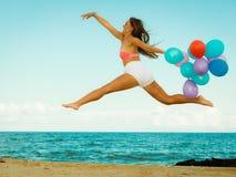 La ragazza che salta con i palloni variopinti sulla spiaggia Immagine Stock Libera da Diritti