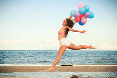La ragazza che salta con i palloni variopinti sulla spiaggia Immagini Stock Libere da Diritti