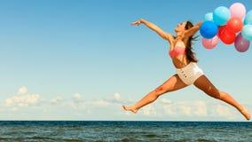 La ragazza che salta con i palloni variopinti sulla spiaggia Fotografie Stock