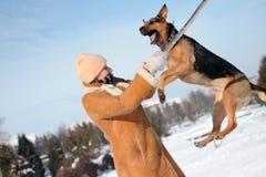La ragazza che salta con il cane contro il cielo blu Fotografie Stock