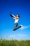La ragazza che salta con il computer portatile Fotografie Stock