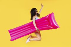 La ragazza che salta con un materasso fotografia stock