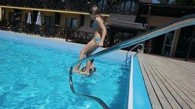 La ragazza che salta e che si tuffa la piscina stock footage