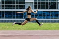 La ragazza che salta il salto triplo Fotografie Stock