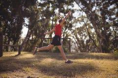 La ragazza che salta nel parco durante la corsa ad ostacoli immagini stock