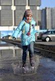 La ragazza che salta nelle pozze Fotografie Stock Libere da Diritti