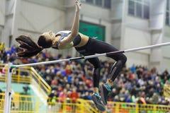 La ragazza che salta sopra la barra nel concorso di salto in alto Fotografia Stock Libera da Diritti