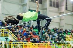 La ragazza che salta sopra la barra nel concorso di salto in alto Immagini Stock