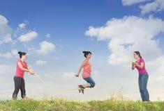 La ragazza che salta sopra una corda Immagini Stock