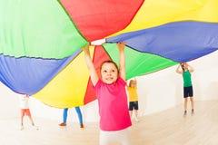 La ragazza che salta sotto la tenda durante i giochi del paracadute immagine stock libera da diritti