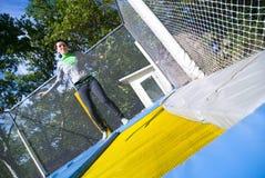 La ragazza che salta su luna-rimbalza Fotografie Stock