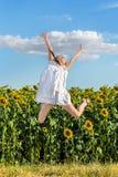 La ragazza che salta su un fondo di un campo dei girasoli Fotografia Stock