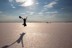 La ragazza che salta sul lago di sale immagini stock libere da diritti