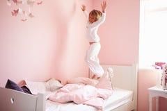 La ragazza che salta sul suo letto Fotografia Stock