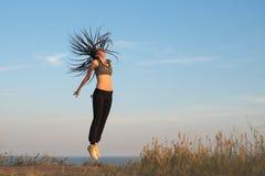 La ragazza che salta sulla spiaggia in scarpe da tennis gialle immagine stock