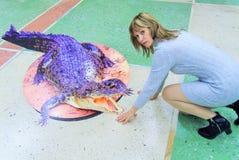 La ragazza che si siede accanto al coccodrillo tirato 3D Fotografie Stock