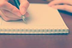 La ragazza che si siede ad una tavola con un taccuino e una penna e scrive Fotografia Stock