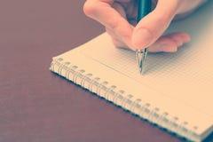 La ragazza che si siede ad una tavola con un taccuino e una penna e scrive Immagine Stock