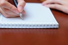 La ragazza che si siede ad una tavola con un taccuino e una penna e scrive Fotografia Stock Libera da Diritti