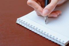 La ragazza che si siede ad una tavola con un taccuino e una penna e scrive Fotografie Stock Libere da Diritti