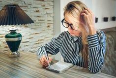 La ragazza che si siede alla tavola e scrive negli importi di un taccuino della carta Fotografie Stock