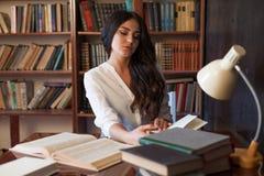 La ragazza che si siede alla tavola che legge un libro sta preparando per l'esame fotografia stock