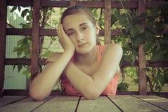 La ragazza che si siede nel giardino, nel gazebo, sul terrazzo di estate Immagini Stock Libere da Diritti