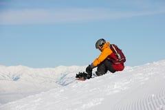 La ragazza che si siede su un pendio e prepara uno snowboard Immagini Stock