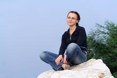 La ragazza che si siede su una roccia fotografie stock libere da diritti