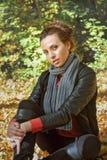 La ragazza che si siede sul giallo lascia nel parco Immagine Stock Libera da Diritti