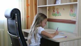 La ragazza che si siede sulla sedia di cuoio nera dalla tavola scrive qualcosa in taccuino dalla penna Fotografie Stock Libere da Diritti