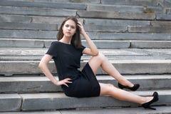 La ragazza che si siede sulle scale Fotografia Stock