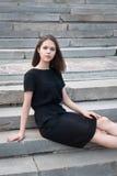 La ragazza che si siede sulle scale Immagini Stock Libere da Diritti