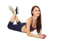 La ragazza che si trova sul pavimento nello sport copre con le cuffie Fotografia Stock Libera da Diritti