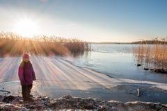 La ragazza che sta ad una riva che esamina il tramonto dell'inverno con il sole si svasa Immagini Stock Libere da Diritti