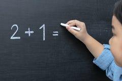 La ragazza che sta pensando il problema per la matematica immagini stock