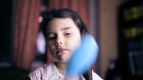 La ragazza che teenager il bambino raddrizza i capelli la pettina archivi video